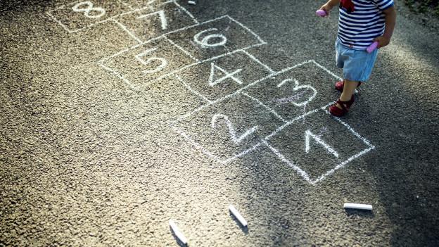 Mädchen spielt Kinder-Hüpfspiel Himmel und Hölle