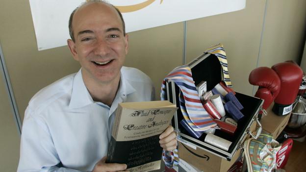 Amazon-Gründer Jeff Bezos zeigt das erste verkaufte Buch.