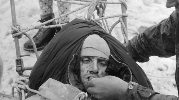 Der gerettete Italiener Claudio Corti stärkt sich am 11. August 1957 mit Brot und heissen Getränken.