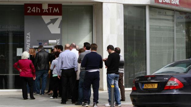 Schlagen vor den Geldautomaten: EZB droht den Geldhahn zuzudrehen.