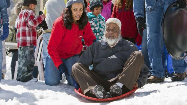 Indischer Tourist testet Schneerutsche auf dem Jungfraujoch.
