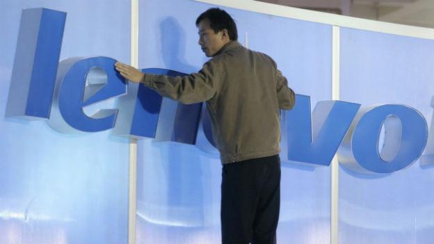 Ein Chinesischer Arbeit befestigt ein Lenovo Schild an einer IT-Messe.