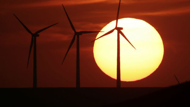 Windräder stehen vor grossem Sonnenball im Hintergrund.