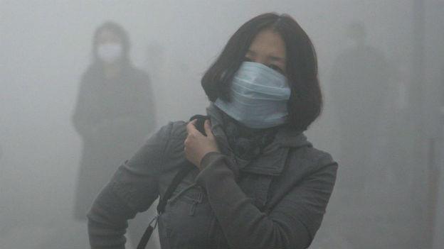 Frau mit Atemmaske im Smog von Harbin.