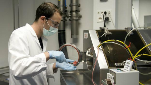 Ein Mann kontrolliert die Lackierung von Tabletten im Labor der Mepha Pharma AG in Aesch.