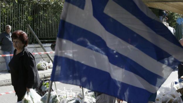Eine grosse griechische Flagge ist im Mittelpunkt zu sehen, daneben 2 Menschen, die mit Früchten und Gemüsten gefüllte Taschen tragen