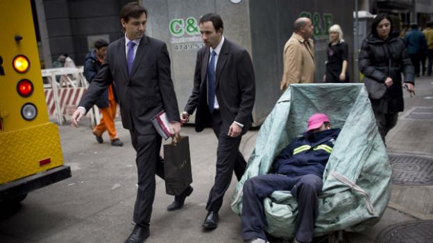 Zwei Manager blicken auf einen Arbeiter, der in seinem Container im Finanzdistrikt von Buenos Aires ein Nickerchen hält.