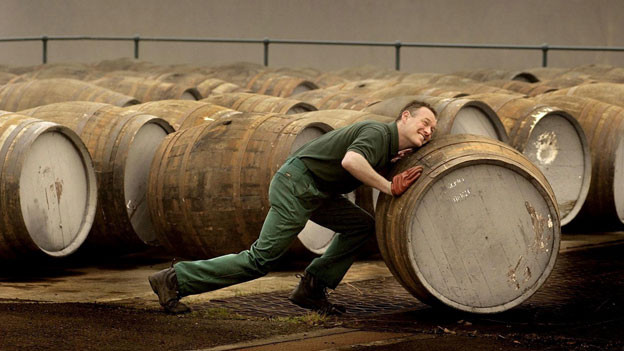 Ein Angestellter der Produktion transportiert Whisky-Fässer.
