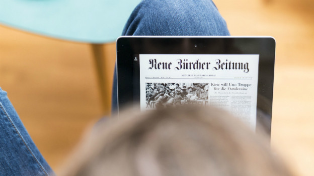 Ein Mann liest die NZZ auf einem iPad.