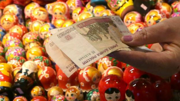 Eine Verkäuferin hält russische Banknoten in ihren Händen.