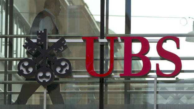 UBS-Signet hängt vor gläserner Wand.