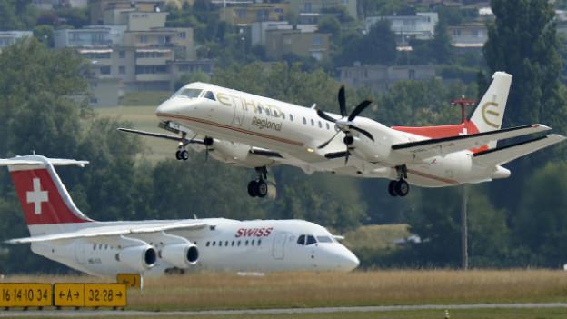 Am Boden wartet ein Flieger der Swiss - auf dem Rollfeld hebt ein Flieger der Etihad Regional ab.