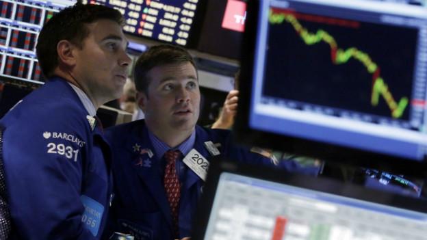 Zwei Börsenmakler beobachten die Kurse an der Wallstreet.