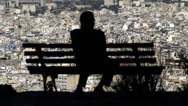 Ein Mann sitzt auf einer Bank. Nur sein Schatten ist sichtbar, im Hintergrund ist die Athener Innenstadt zu sehen.