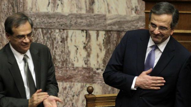 Der Griechische Premier Samaras und Finanzminister Chardouvelis stehen nebeneinander. Chardouvelis klatscht, Samaras hält sich die rechte Hand in einer Art Dankesgeste an die Brust.