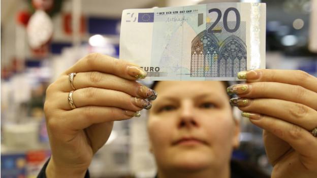 Eine Kassiererin in einem litauischen Supermarkt prüft eine 20 EURO-Note.