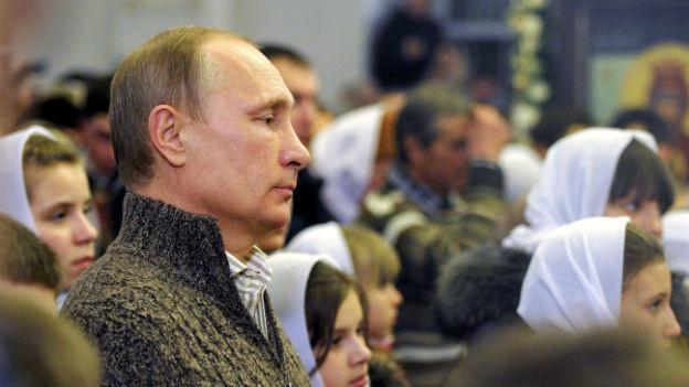 Russischer Präsident Putin steht zwischen Mädchen mit Kopftüchern.