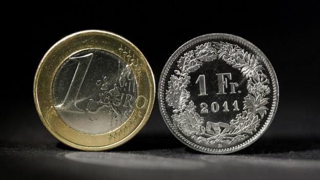Vor schwarzem Hintergrund sind eine Ein-Euro-Münze und eine Ein-Franken-Münze abgebildet.