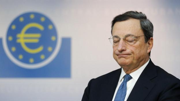 EZB-Chef Draghi verzieht gesicht, im Hintergrund Euro-Symbol.