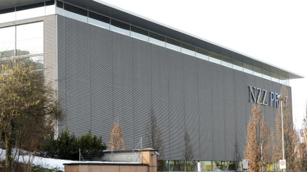 Das NZZ-Druckzentrum in Schlieren von aussen, mit Sicht auf den Parkplatz vor dem Gebäude.