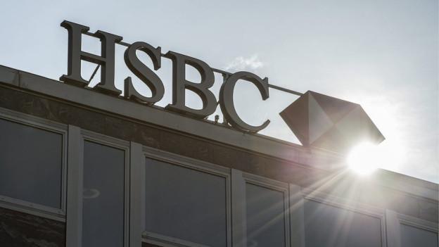 Das Logo der HSBC auf einem Hausdach im Gegenlicht.
