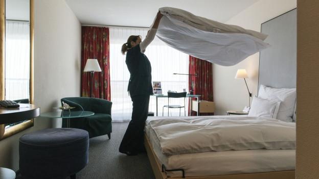 Das Bild zeigt ein Hotelzimmer, in welchem eine Zimmerfrau das Duvet ausschüttelt.