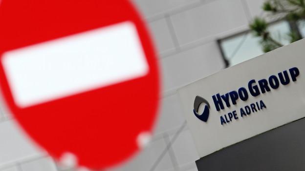 Ein Einbahnstrassenschild unscharf im Vordergrund, dahinter der blaue Schriftzug «Hypo Group Alpe Adria»