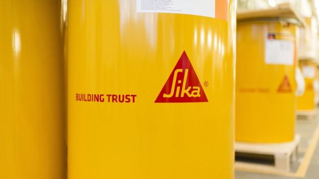 Grossaufnahme eines gelben Fasses, auf dem das Sika-Logo zu sehen ist.
