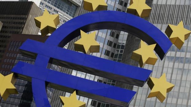 Logo der EZB, im Hintergrund Hochhausfassade.