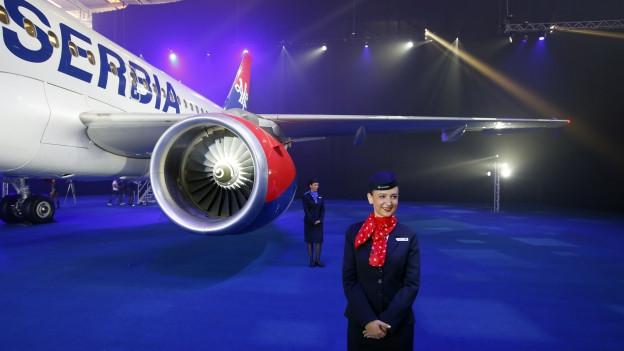 Das Bild zeigt ein Flugzeug der Air Serbia in einem Hangar, davor eine Flight Attendant