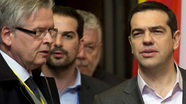 Griechenlands Premierminister Tsipras spricht mit einem anderen Mann; im Hintergrund sind mehrere Flaggen erkennbar.