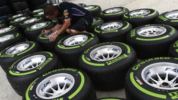Ein Angestellter des Formel-1-Teams Red Bulls präpariert Pirelli-Reifen am Grand Prix von Malaysia. Aufnahme vom März 2014.