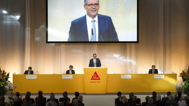 Ein grosser Bildschirm überträgt die Rede von Paul Hälg an der Sika-GV.