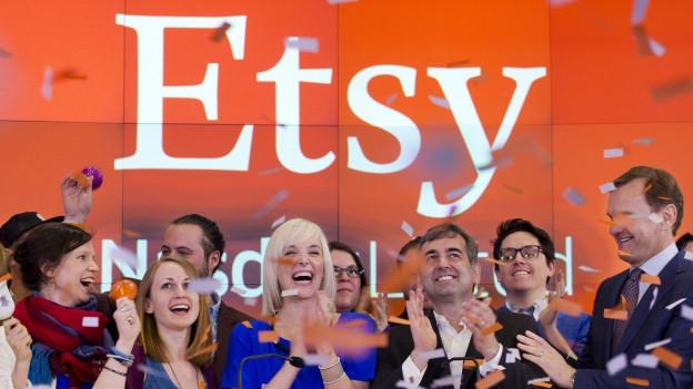 Jubelnde Menschen vor ETSY-Firmen-Logo.