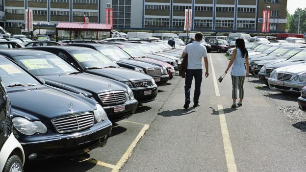 Das Bild zeigt den Parkplatz eines Auto-Occasions-Händlers und ein Paar, das ein Auto sucht.