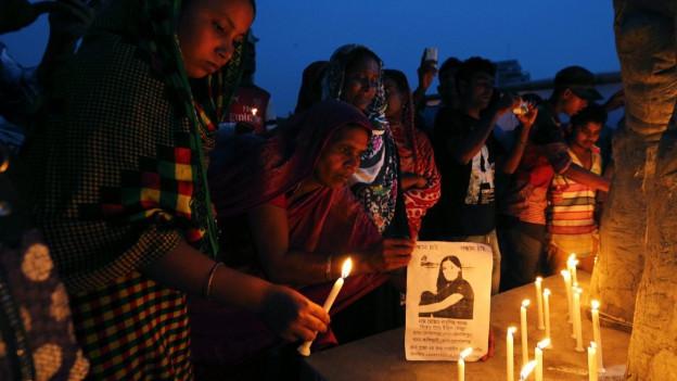 Gedenkfeier: eine Frau hält eine brennende Kerze in der Hand und ist dabei, sie auf einen grossen Stein zu stellen, auf dem schon weitere Kerzen brennen.