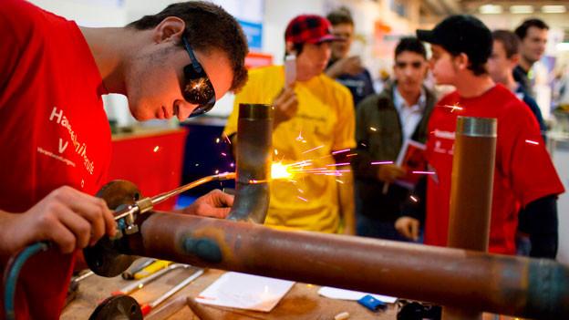 Lehrlinge löten am Stand der Metallbauschlosser an der Berufsmesse 2007 in Zürich ein Rohr.
