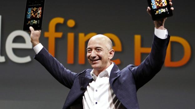 Mann hält zwei Tablet-Computer in die Höhe.