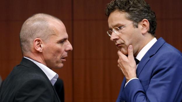 Yanis Varoufakis und Jeroen Dijsselbloem sprechen miteinander, beide wirken nachdenklich.