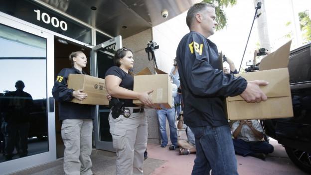 Drei FBI-Beamte tragen konfisziertes Material aus dem Gebäude der CONCACAF in Florida.