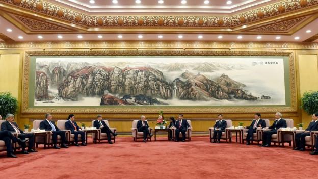 Umgeben von weiteren Delegierten, spricht Bundesrat Schneider-Ammann an der Unterzeichnungs-Zeremonie mit dem chinesischen Präsidenten Xi Jinping.