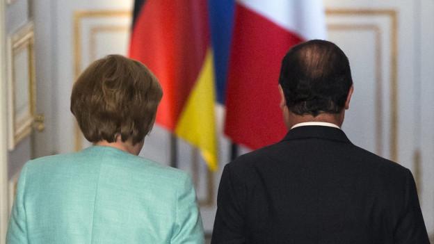 Angela Merkel und François Hollande auf dem Weg in ein Sitzungszimmer.
