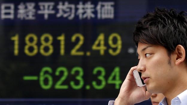 Das Bild zeigt einen Mann in Tokio vor einer elektronischen Anzeige mit dem aktuellen Stand beim Nikkei-Index.