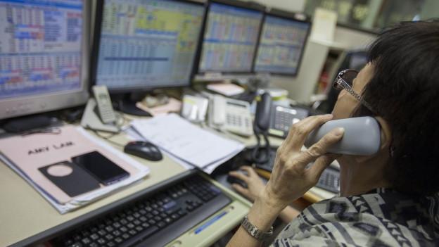 Eine Frau telefoniert während ihre Computerbildschirme sinkende Börsenindizes zeigen.