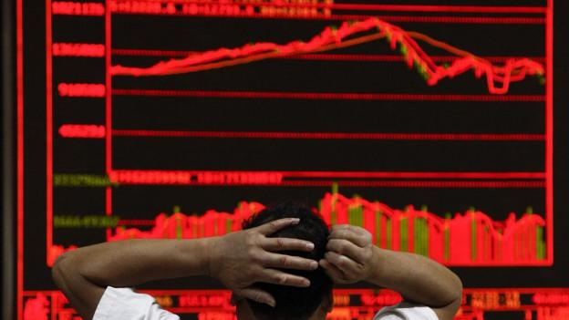 Aufnahme eines Börsenhändlers von hinten in Peking, der die Bewegungen an Chinas Börsen beobachtet.