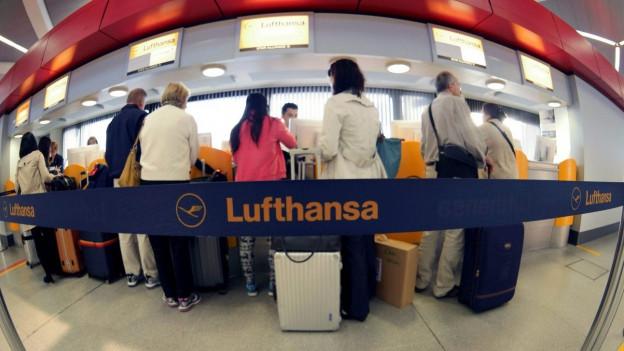 Menschen stehen hinter einem Absperrband von Lufthansa am Flughafen.
