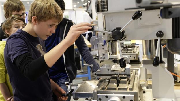 Auf dem Bild sieht man einen Jugendlichen, der an der Berufsmesse 2014 in Zürich an einer Maschine hantiert