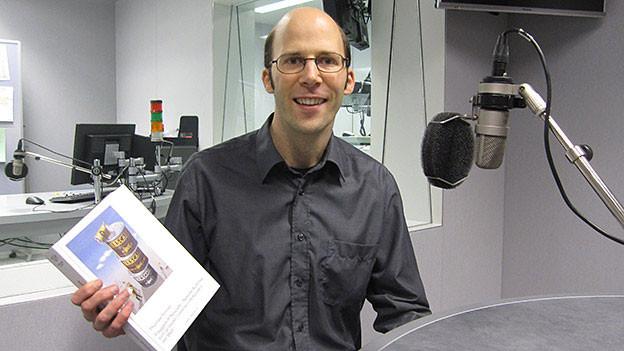 Thomas Fenner zeigt im Radiostudio Bern sein neues Buch über Nestlé.