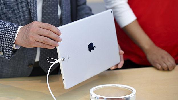 Eine Männerhand hält ein weisses iPad.