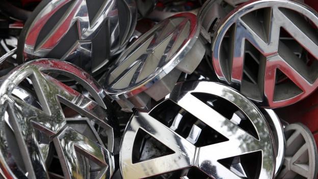 Übereinander geworfene VW-Plaketten.